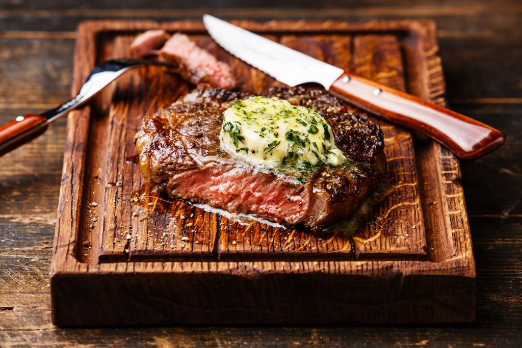 Grilled medium rare steak with herb butter